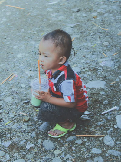 Side view full length of boy with drink glass on field