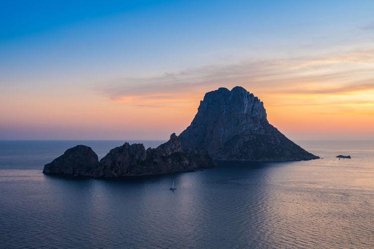 Scenic view of es vedrà island at sunset in mediterranean sea.ibiza