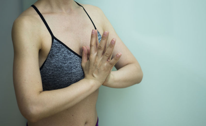 Midsection of woman with hands clasped meditating against wall