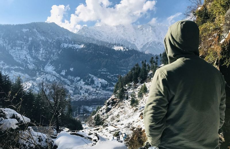 Rear view of man looking at snowcapped mountains