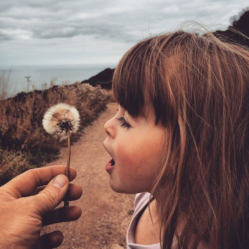 Holding Childhood Headshot Focus On Foreground Sea Person Person Little Girl Fatherhood Moments Dandylion Kid Child Countryside Nature Flower Beauty In Nature Fairy Flower Cloud Innocence In Front Of Human Face Sky Tranquility Day Fairy