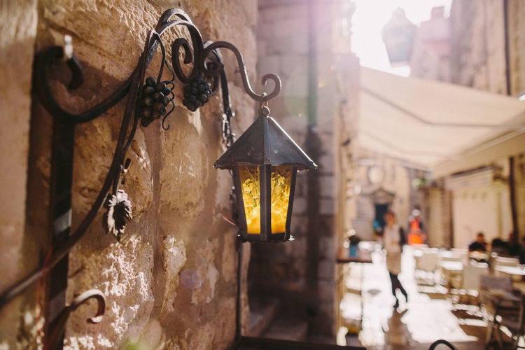 old vintage lamp in old town Croatia Old Town Architecture Art And Craft Building Building Exterior Built Structure Close-up Day Dubrovnik Electric Lamp Focus On Foreground Hanging Illuminated Incidental People Lantern Lens Flare Lighting Equipment Metal Nature Old Buildings Outdoors Sunbeam Sunlight