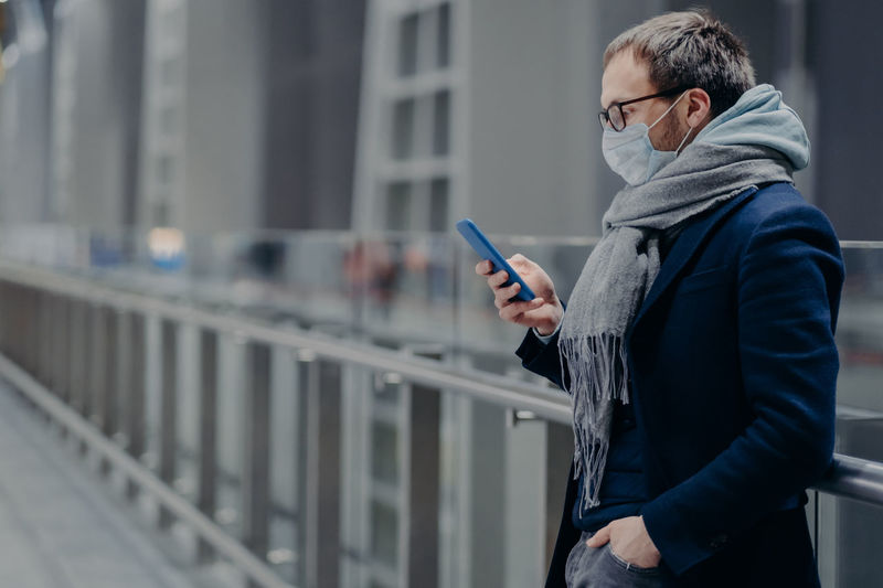 Man using mobile phone while standing on railing during winter