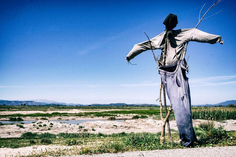 Man standing on field against blue sky