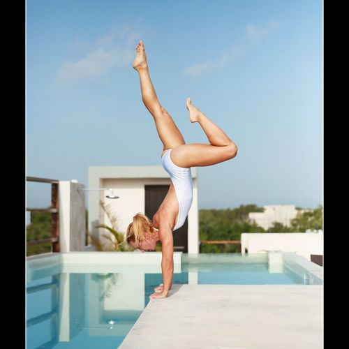 Full Length Of Woman In Bodysuit Practicing Yoga By Pool