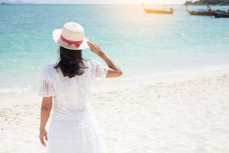 Rear View Of Woman With Sun Hat Standing On Beach