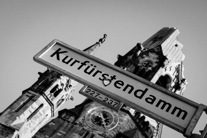 Low angle view of kurfurstendamm sign against kaiser wilhelm memorial church