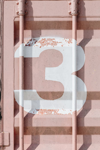 White silk-screen printing of number 3 on a pink shipping container