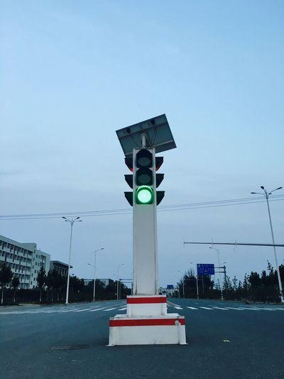Illuminated traffic light on street against sky