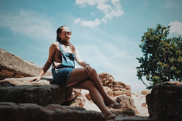 Low angle view of woman sitting on sunny day