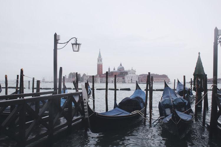 Gondolas moored at sea against sky