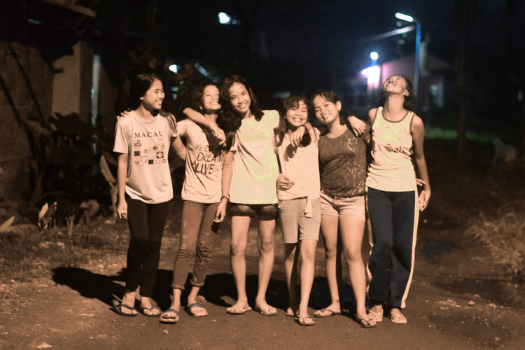 Full length portrait of friends standing at night