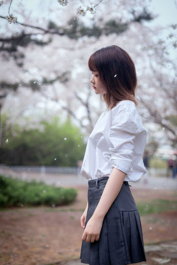 Side view of young woman standing against trees