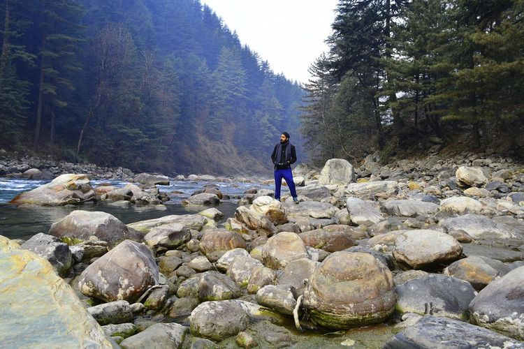 Full length of man standing on rocks at riverbank in forest