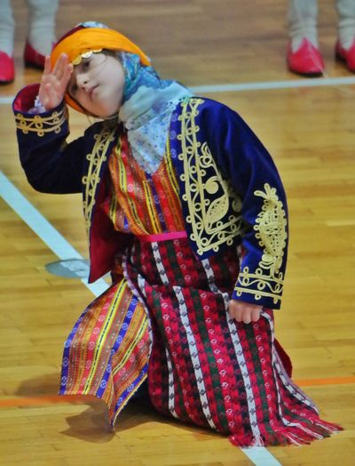 Girl in folk dance dress performing on stage
