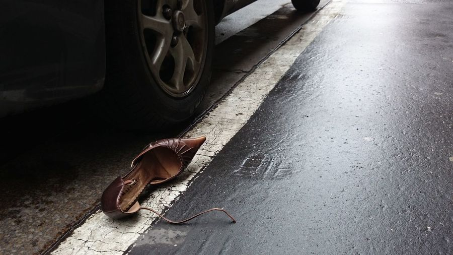 High angle view of lost footwear by car on street