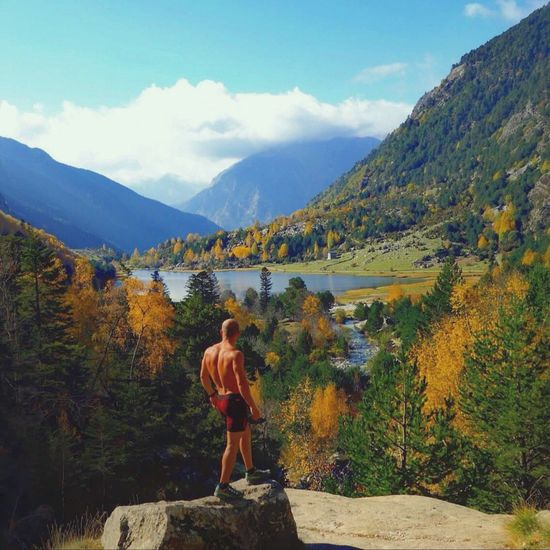 Rear view of shirtless hiker standing on rock against sky
