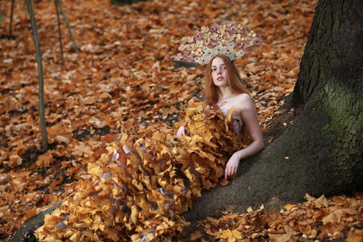 Young woman wrapped in autumn leaves against tree