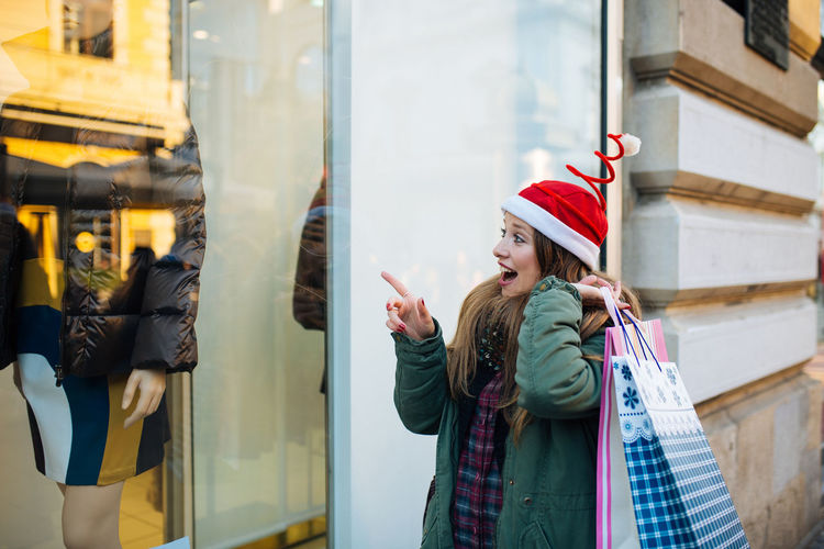 Surprised Woman Pointing Window Display Of Store In City