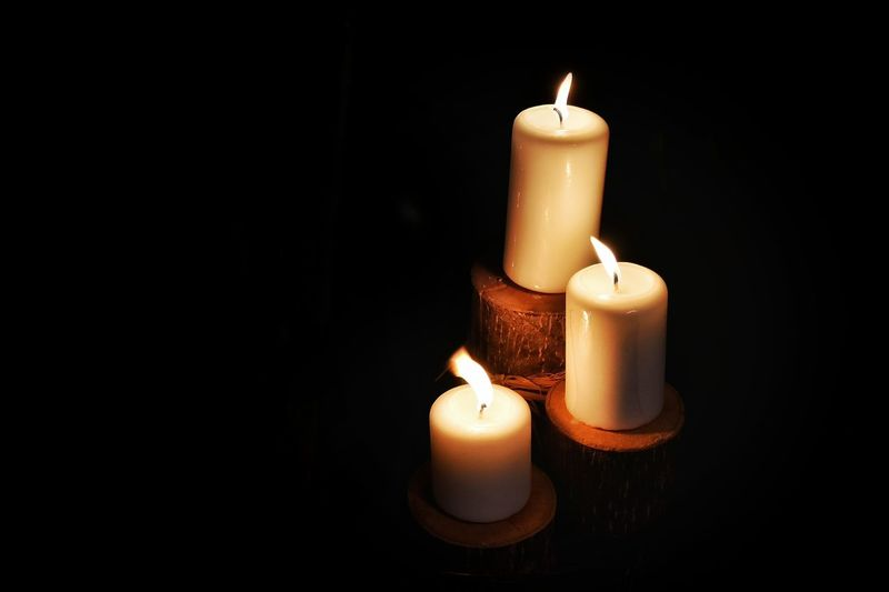 High angle view of illuminated candle against black background