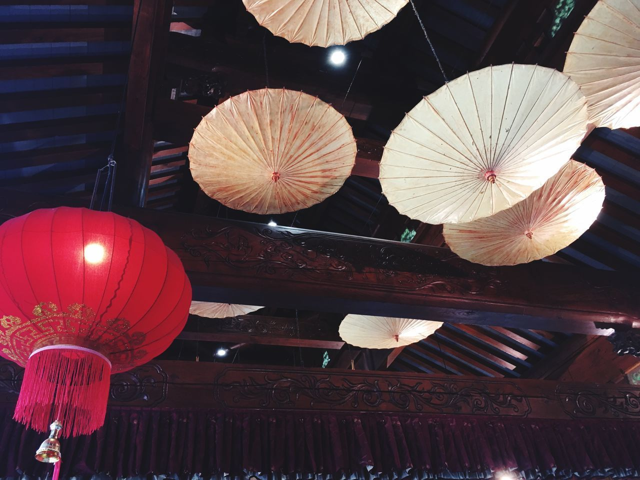 LOW ANGLE VIEW OF ILLUMINATED LANTERNS HANGING FROM ROOF