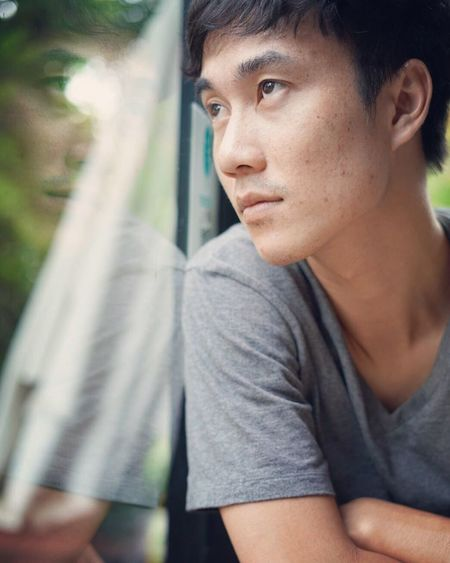 Close-up of thoughtful man looking through window