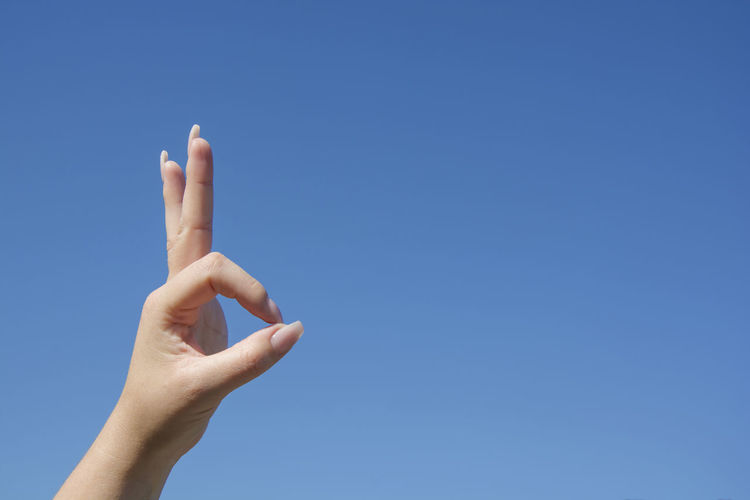 Woman hand show O.K. sign on blue sky background, symbol language body Hand Human Body Part Sky Body Part One Person Clear Sky Finger Human Finger Lifestyles Blue Day Copy Space Outdoors Woman Sign Symbol Language