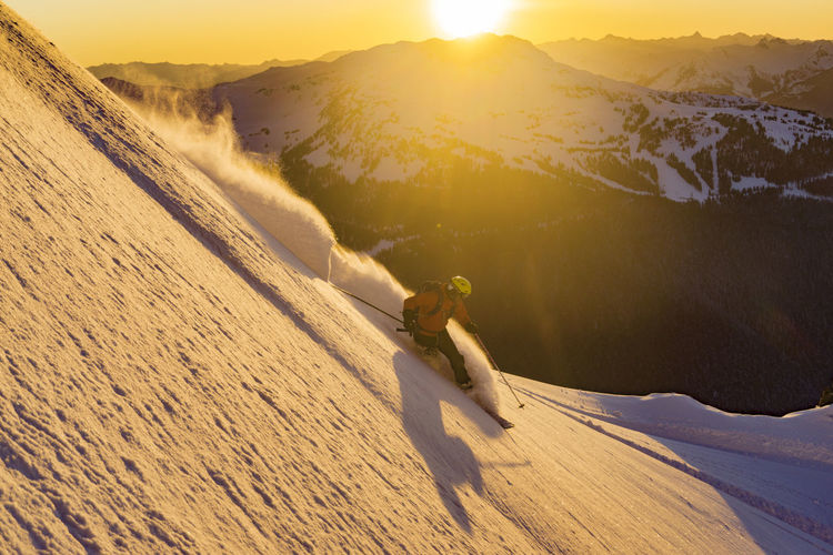 Man skiing on snow during sunset