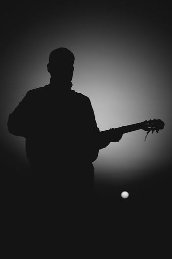 Silhouette man playing guitar against sky