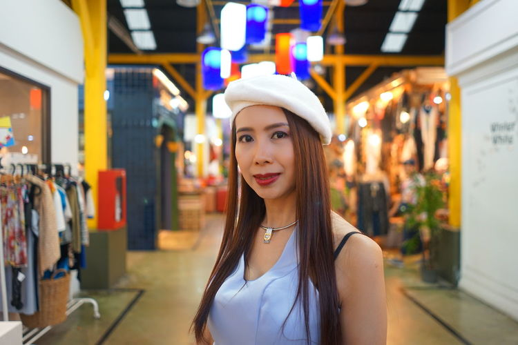 Portrait of woman standing in illuminated store