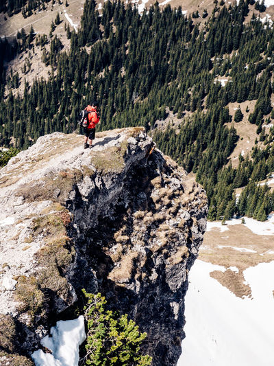 Hiker Standing On Rock Formation Against Snowcapped Mountain
