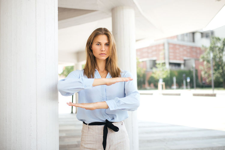 Portrait of young woman standing against built structure