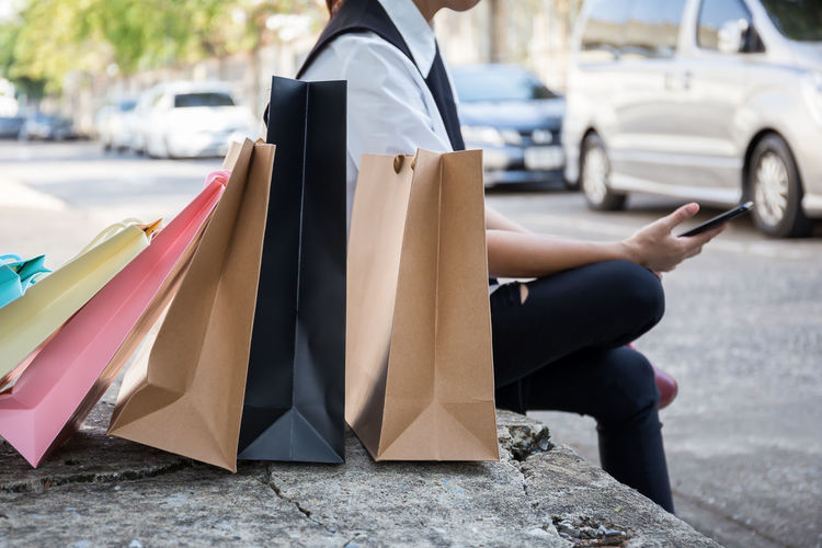 Midsection Of Person Sitting With Shopping Bags On Sidewalk