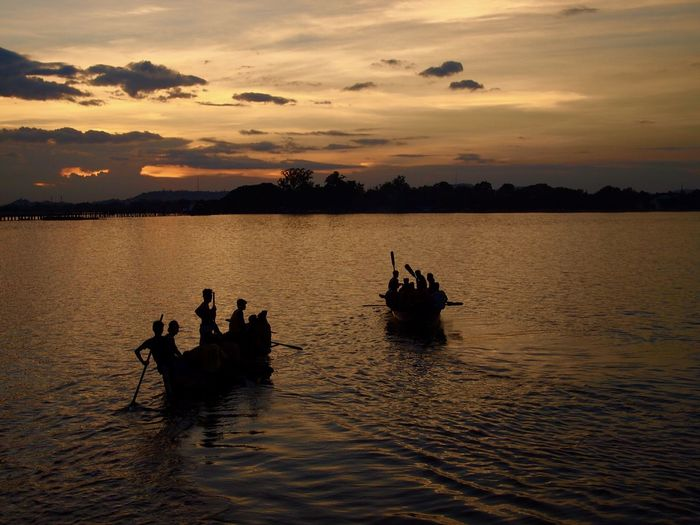 Silhouette people on rowboats in lake against sky during sunset