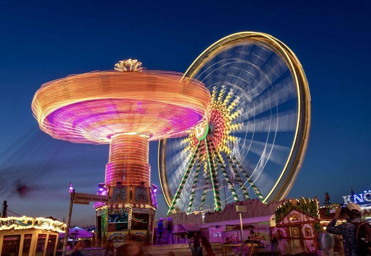 Illuminated amusement park rides spinning against sky at night