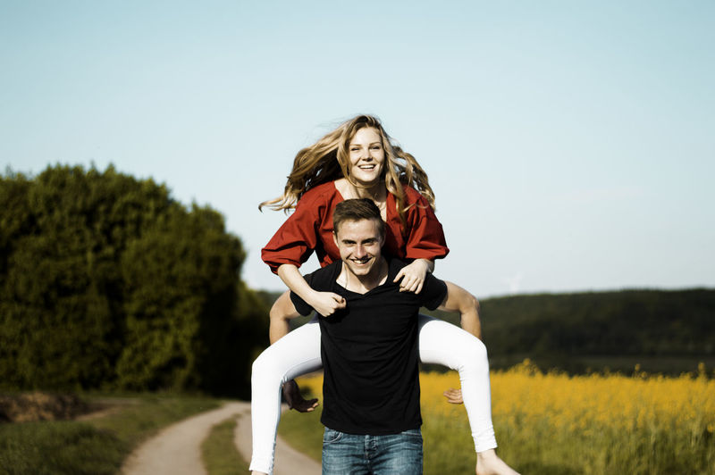 Portrait Of Man Piggybacking Woman On Road Against Sky