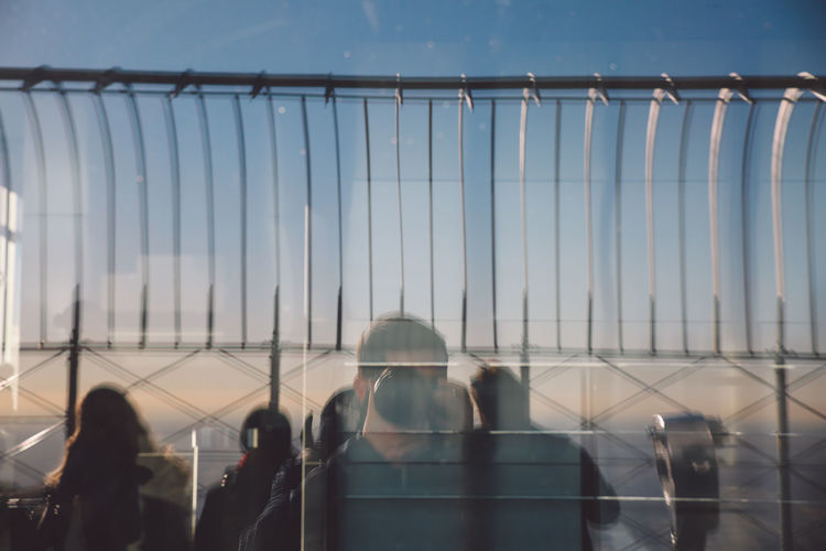 Reflection Of Photographer With Tourists On Glass Window Of Empire State Building