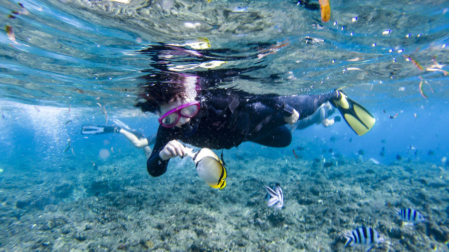 Full Length Side View Of Woman Scuba Diving Undersea