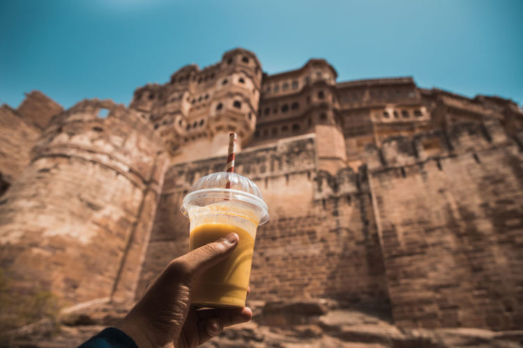 Midsection of person holding drink in a hot summer against a built structure of a fort