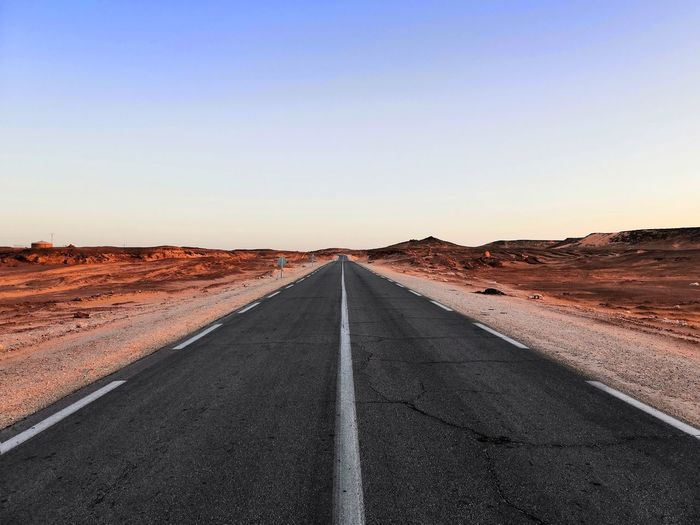 Diminishing perspective of empty road at desert against clear sky