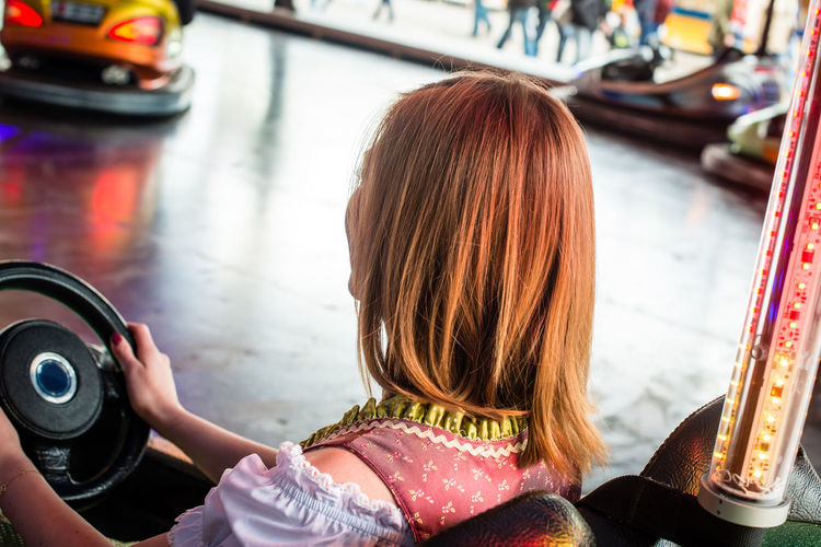 Rear view of woman sitting in bumper car at amusement park
