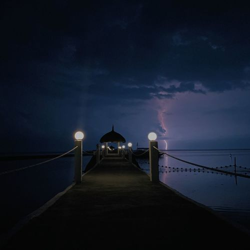 Illuminated pier on sea against sky at night