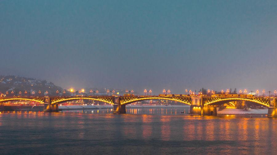Illuminated bridge over river against sky in city at night