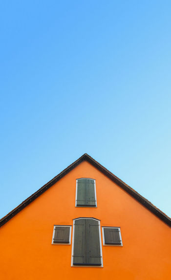 Orange house with pitched roof  on a blue sky. german home with orange walls and timber shutters.