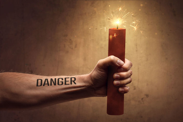 Human hand holding lit candle