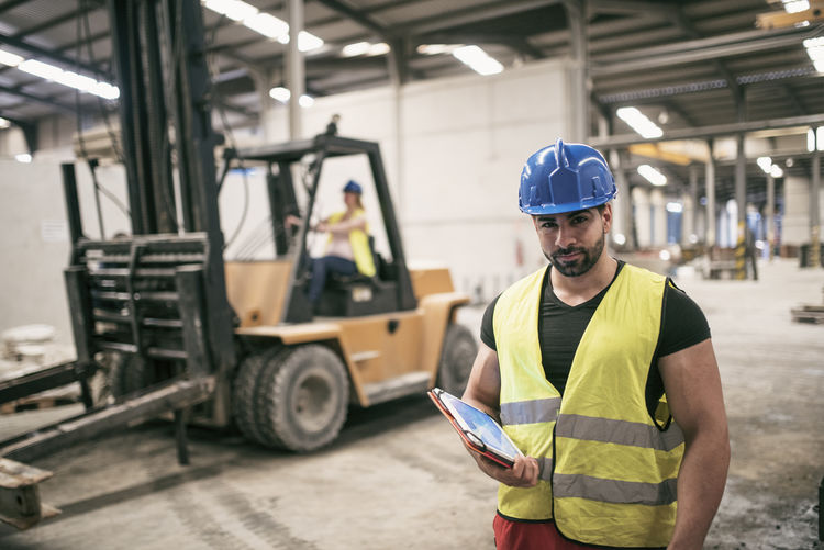Portrait of young man using digital tablet while standing at factory