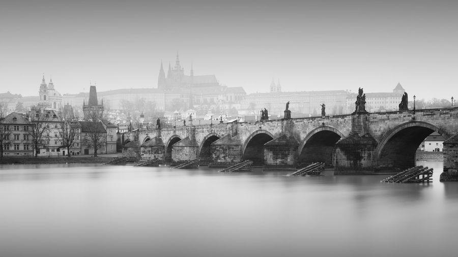 Charles bridge on vltava river in city against sky