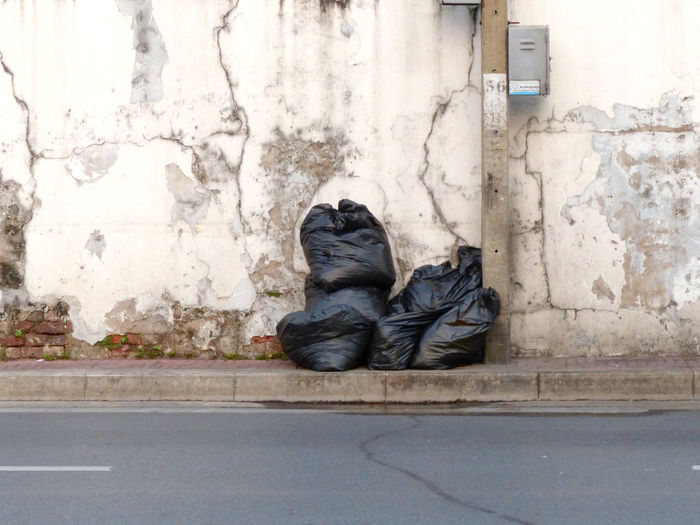 Garbage bags against weathered wall
