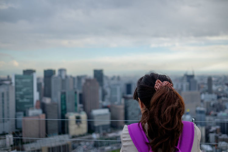 Rear View Of Woman Standing In Front Of Cityscape
