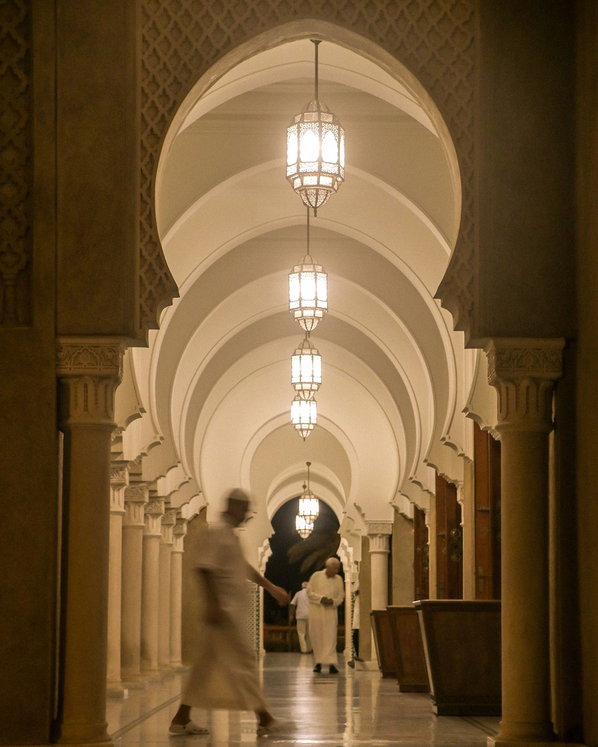 architecture, arcade, arch, built structure, corridor, walking, indoors, illuminated, architectural column, building, men, lighting equipment, real people, motion, in a row, adult, women, people, lifestyles, two people, ceiling, couple - relationship, electric lamp